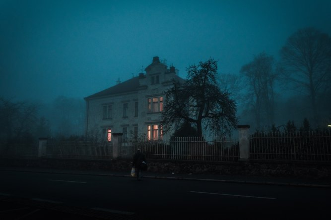 Creepy house at dusk with lights lit