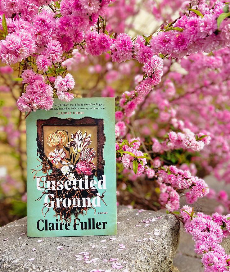 Hardback copy of Unsettled Ground on a stone wall in front of a pink flowering tree.